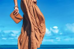 Beautiful young woman in elegant dress with clutch on the beach royalty free stock image