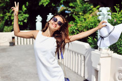 Beautiful young woman in elegant hat and sunglasses posing outdo Stock Images