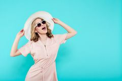 Beautiful young woman in elegant pale pink dress, sunglasses and summer hat. Studio portrait of fashionable woman. Stock Photos
