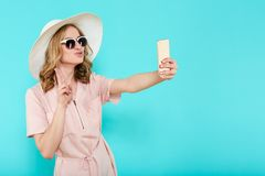 Beautiful young woman in elegant pale pink dress, sunglasses and summer hat taking selfie. Studio portrait of fashionable woman. Stock Photo