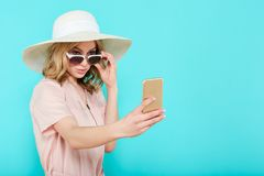 Beautiful young woman in elegant pale pink dress, sunglasses and summer hat taking selfie. Studio portrait of fashionable woman. Stock Image