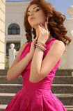 Beautiful young woman in elegant pink dress posing in summer park Royalty Free Stock Photography