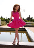 Beautiful young woman in elegant pink dress posing in summer park Stock Photography