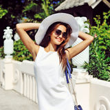 Beautiful young woman in elegant white dress and hat posing outd Stock Photos