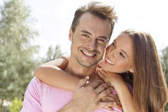 Beautiful young woman embracing man from behind in park Stock Photo