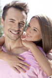 Beautiful young woman embracing man from behind in park Royalty Free Stock Photography