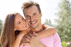 Beautiful young woman embracing man from behind in park Royalty Free Stock Images