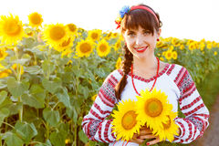 Beautiful young woman in embrodery holding three sunflowers Stock Image