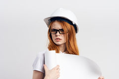 Beautiful young woman engineer on white  background holds blueprints Royalty Free Stock Photos