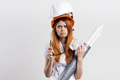 Beautiful young woman engineer on white  background holds blueprints Stock Photography