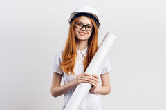 Beautiful young woman engineer on white  background holds blueprints Royalty Free Stock Images