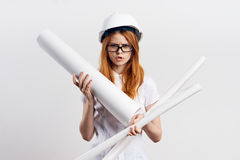 Beautiful young woman engineer on white  background holds blueprints Stock Image