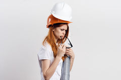 Beautiful young woman engineer on white isolated background holds blueprints Royalty Free Stock Photography