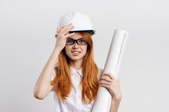 Beautiful young woman engineer on white isolated background holds blueprints Stock Image