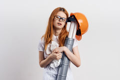 Beautiful young woman engineer on white isolated background holds blueprints Royalty Free Stock Photo