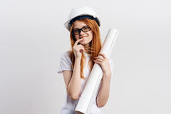 Beautiful young woman engineer on white isolated background holds blueprints Stock Photo