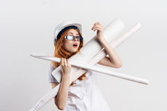 Beautiful young woman engineer on white isolated background holds blueprints Royalty Free Stock Image