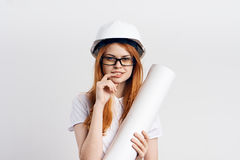 Beautiful young woman engineer on white isolated background holds blueprints Stock Photos