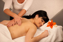 Beautiful young woman enjoing a massage treatment in wellness Stock Image