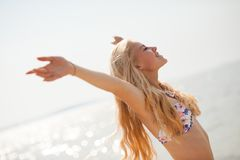 Beautiful young woman enjoy on beach with her arms up - success. Concept stock image
