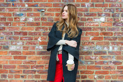 Beautiful young woman enjoy drinking coffee outdoors near red brick wall wearing warm autumn clothes and holding paper coffee cup. Stock Photos