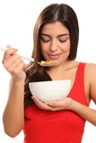 Beautiful young woman enjoying breakfast cereal Royalty Free Stock Image