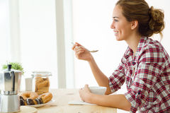 Beautiful young woman enjoying breakfast in her new home. Royalty Free Stock Images