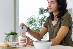 Beautiful young woman enjoying breakfast at home. Stock Image