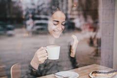 Beautiful young woman enjoying coffee cappuccino with foam near window royalty free stock photo