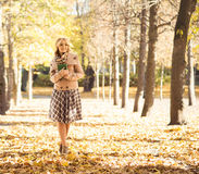 Beautiful young woman enjoying coffee smell in the park in autumn Stock Photo