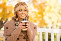 Beautiful young woman enjoying coffee smell in the park in autumn Stock Photos