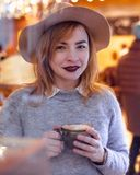 Smiling woman in cafe holding a cup with coffee. Woman wearing in sweater and hat stock photo