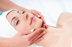 Beautiful young woman enjoying facial massage. In spa salon with eyes closed Royalty Free Stock Photography