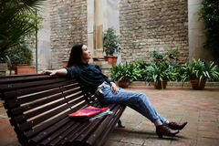 Beautiful young woman enjoying her leisure time outdoors. Shot of a thoughtful young female student leaning on a campus bench and resting after classes royalty free stock photos