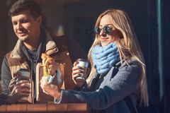 Beautiful young woman enjoying her lunch croissant with coffee while she standing outdoors cafe and communicate with friends. royalty free stock image
