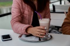 Beautiful young woman enjoying latte coffee in cafe. royalty free stock image