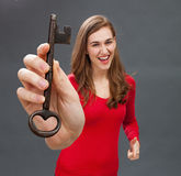 Beautiful young woman enjoying laughing with a big old key Royalty Free Stock Photo