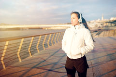 Beautiful young woman enjoying a moment after running. Listening to music Stock Image