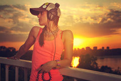 Beautiful young woman enjoying the music. Has large headphones and wearing cap. Toned image and low light effect Stock Images