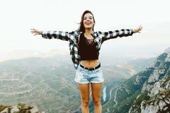 Beautiful young woman enjoying nature at mountain peak. stock images