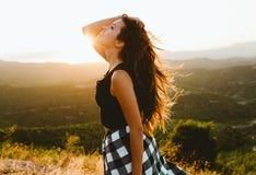 Beautiful young woman enjoying nature at mountain peak. royalty free stock image