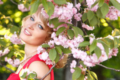 Beautiful young woman enjoying near blooming Japanese cherry tre Royalty Free Stock Images