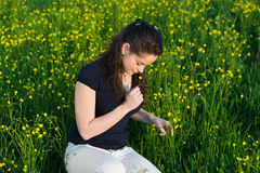Beautiful young woman enjoying the scent of flowers . Royalty Free Stock Image