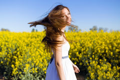 Beautiful young woman enjoying spring in a field. Royalty Free Stock Image