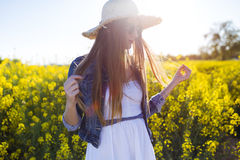 Beautiful young woman enjoying spring in a field. Royalty Free Stock Photo