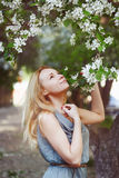 Beautiful young woman is enjoying by spring flowers Stock Photos