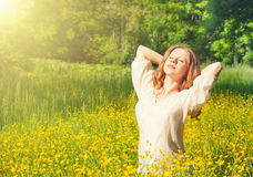 Beautiful young woman enjoying the summer sun. Outdoors in the park Stock Images