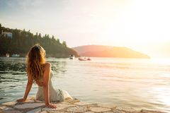 Beautiful young woman enjoying the sunset at the sea Stock Images