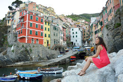 Beautiful young woman enjoying the view of Riomaggiore in the UNESCO World Heritage Site Cinque Terre, Five Lands, Italy Stock Photo