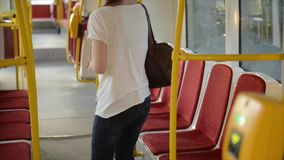 Beautiful young woman enters tram and sits on the seat. Train departure and ride to next station. Urban transport stock video